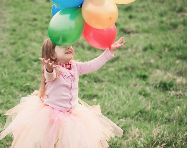 Ragazza felice con palloncini all'aperto