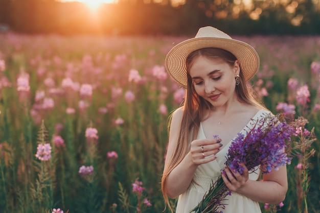 Una ragazza felice con bouquet cammina attraverso un prato in fiore. amore e fioritura primaverile
