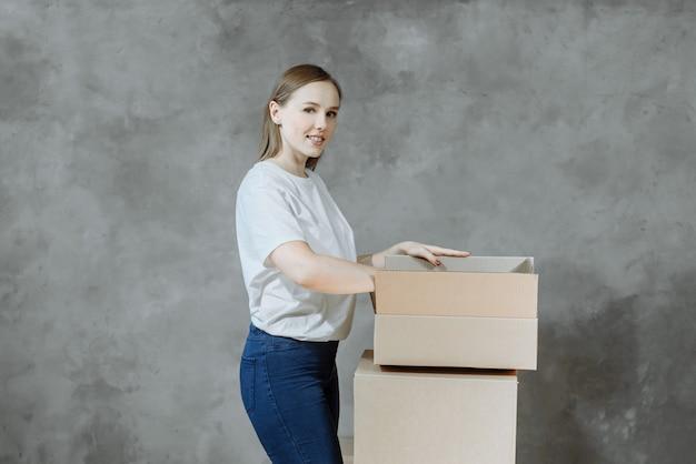 Ragazza felice con scatole per trasferirsi in un nuovo appartamento.
