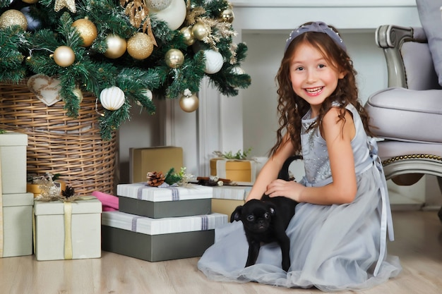 Ragazza felice con un simpatico cane di razza grifone sullo sfondo di un bellissimo albero di natale dorato con regali in sala festiva per buon natale e felice anno nuovo. momenti caldi d'atmosfera in famiglia con regali