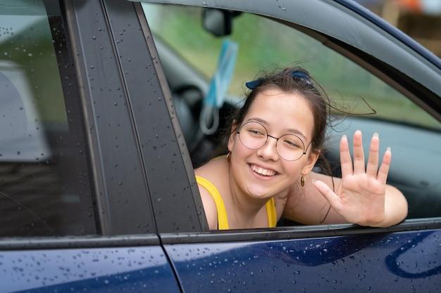Ragazza felice con gli occhiali che guarda fuori dal finestrino della macchina sorridendo e salutando