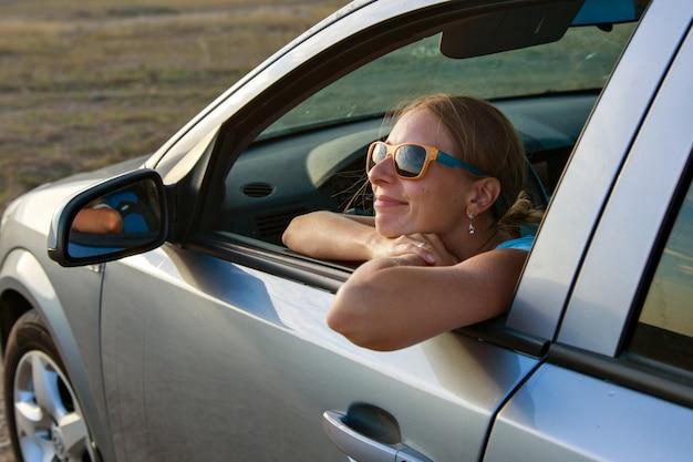 La ragazza felice con gli occhiali guarda fuori dall'auto