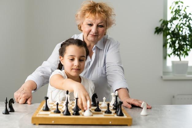 Ragazza felice con la nonna seduta al tavolo e giocare a scacchi.