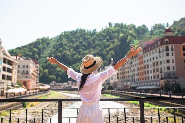 Ragazza felice con il cappello sull'argine di un fiume di montagna in una città europea.