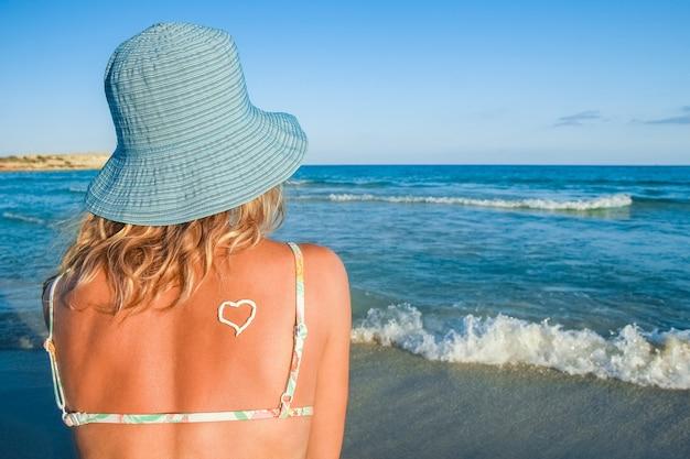 Ragazza felice con un cuore sulla schiena in riva al mare all'aperto