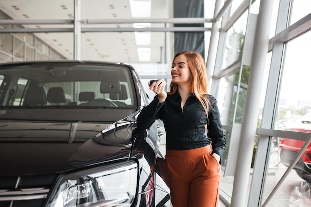 Ragazza felice con una chiave vicino alla nuova auto