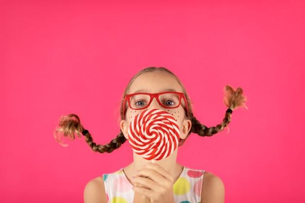 Ragazza felice con lecca-lecca contro il muro rosa.