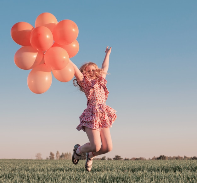 Ragazza felice con palloncini arancioni all'aperto