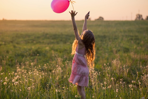 Ragazza felice con l'aerostato rosa esterno