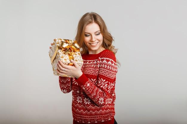 Ragazza felice con un sorriso in un maglione rosso con un ornamento che tiene un regalo