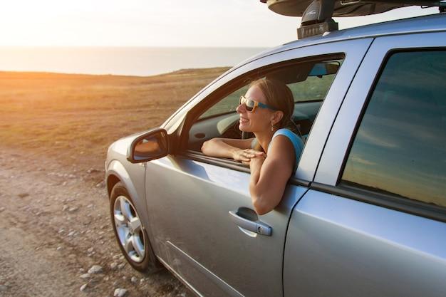 Ragazza felice con gli occhiali da sole che guarda fuori dal finestrino della sua auto in uno splendido sfondo al tramonto