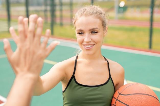 Ragazza felice con il sorriso a trentadue denti che fa il gesto di batti il cinque con la sua amica prima o dopo la partita di basket