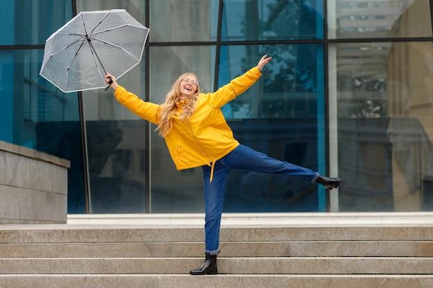Ragazza felice con un ombrello in città d'estate