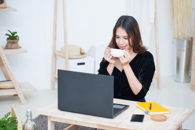 La scrittura felice della ragazza sul taccuino guarda lo schermo del laptop ascolta e impara la classe in linea a casa