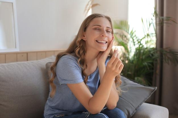 La fidanzata felice guarda l'anello di fidanzamento dopo la proposta seduta su un divano nel soggiorno di casa.