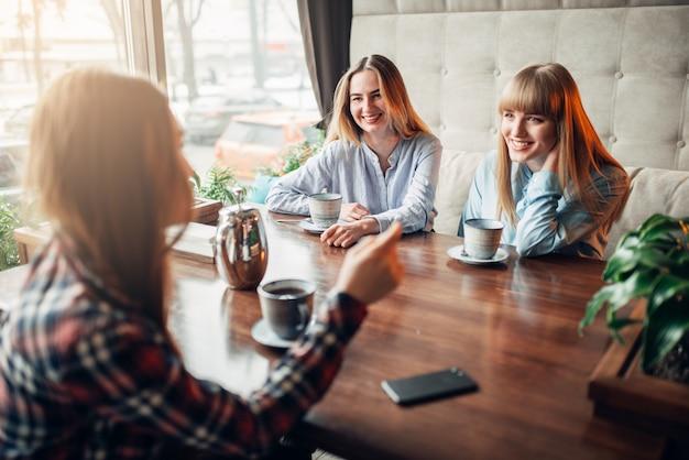 Amiche felici beve caffè al tavolo nella caffetteria. amici femminili che si siedono nel ristorante, riunione dei pettegolezzi
