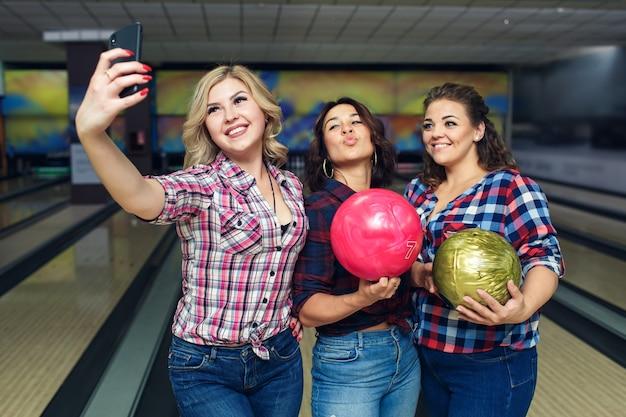 Le amiche felici prendono selfie con lo smartphone al bowling.