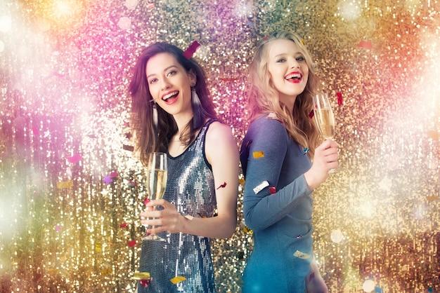 Le ragazze felici bevono spumante per festeggiare il nuovo anno