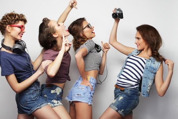 Amici di ragazze felici che scattano alcune foto, su sfondo grigio
