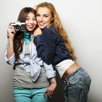 Amiche felici che scattano alcune foto, con la fotocamera, su grigio