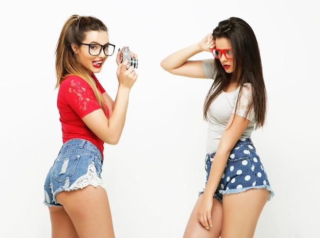 Amici di ragazze felici che scattano alcune foto con la fotocamera, su sfondo bianco