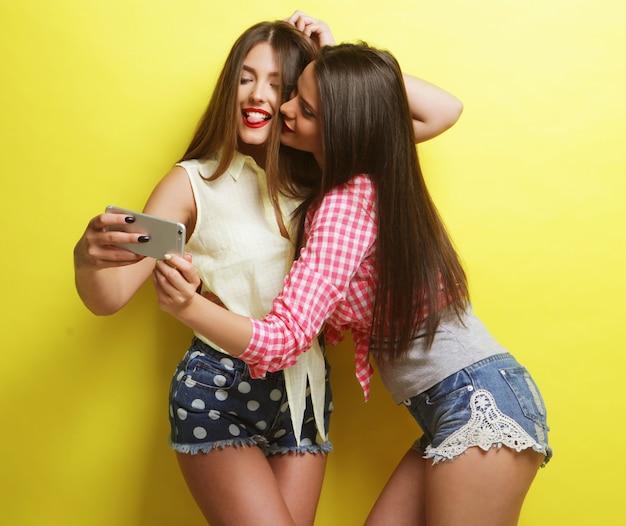 Amiche felici che scattano delle foto, su sfondo giallo