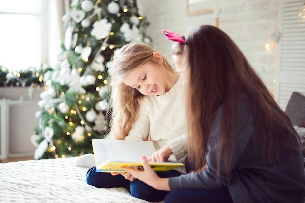 Ragazze felici che si divertono a natale leggendo un libro insieme
