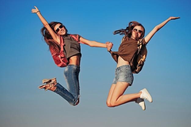 Ragazze felici che saltano sul cielo
