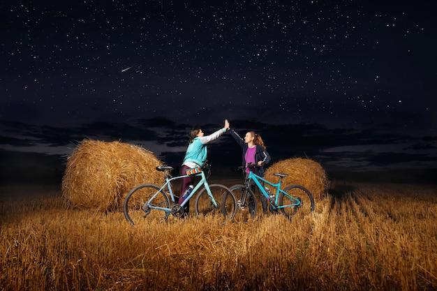 Ragazze felici con le biciclette che danno il cinque l'un l'altro nel campo con i mucchi di fieno. cielo stellato.