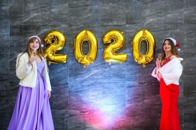 Ragazze felici con champagne e mongolfiere dorate in eleganti abiti da sera che celebrano il nuovo anno