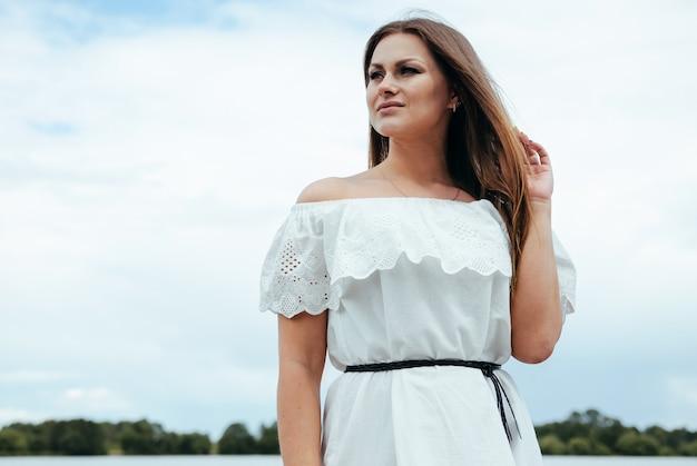 Bella ragazza affascinante felice in un vestito dalla luce bianca su un fondo di un cielo.