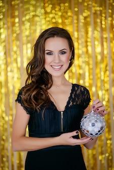 Felice donna affascinante a una festa d'oro con una mini palla da discoteca nelle sue mani. festaioli