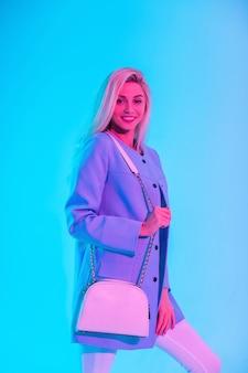 Felice giovane donna sorridente affascinante in abito da lavoro brillante alla moda, look con blazer blu e borsa in posa in studio su sfondo chiaro rosa neon colorato