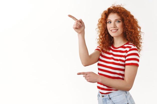 Felice bella rossa riccia donna femminile t-shirt a righe che punta l'indice sinistro guarda la telecamera divertita sorride chiedendo consiglio facendo scelta, raccogliendo prodotti negozio