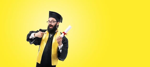 Laureato felice che punta al diploma su sfondo giallo, concetto di completamento con successo degli studi, mock-up panoramico con spazio per il testo