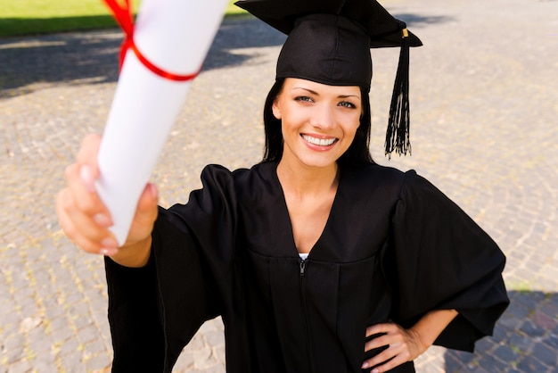Felice laureato con diploma. vista dall'alto di una giovane donna felice in abito da laurea che mostra il suo diploma e sorride