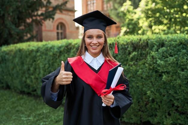 Esposizione felice della donna laureata come alla macchina fotografica con il diploma in vestito di graduazione.