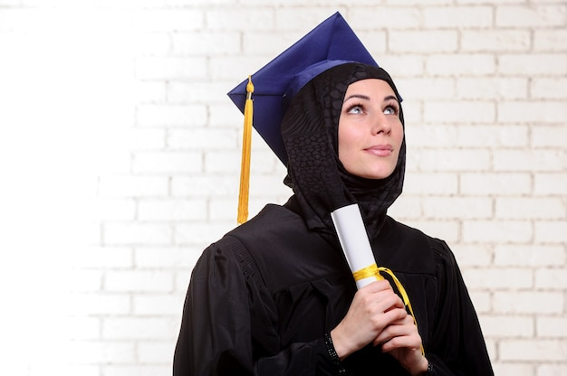 Felice studentessa musulmana laureata posa con diploma indoor