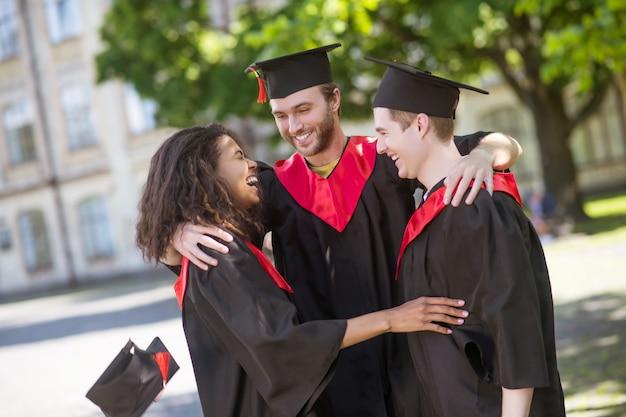 Laureati felici. tre laureati che si abbracciano e discutono della loro laurea