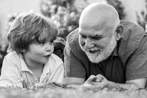 Nonno e nipote felici che si rilassano insieme. festa del papà. ragazzo carino con papà che gioca all'aperto