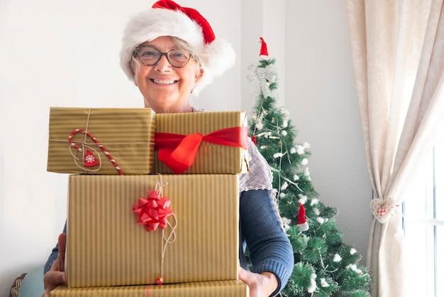 Una nonna felice che tiene molti regali di natale per la famiglia legata con un fiocco rosso - buon natale a casa per un anziano pensionato che si gode le vacanze