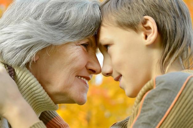 Nonna felice con il ragazzo che riposa nel parco autunnale