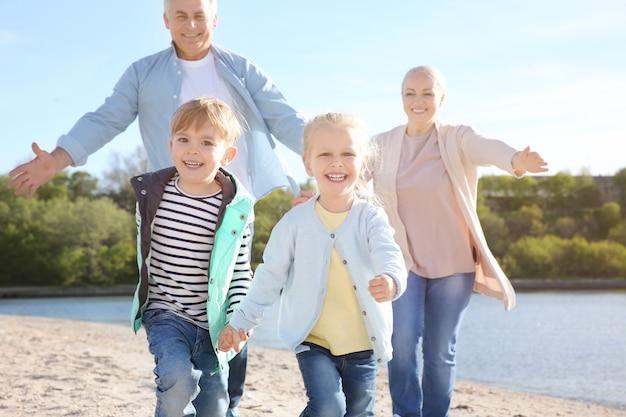 Nonni felici che giocano con i bambini piccoli sulla riva del fiume
