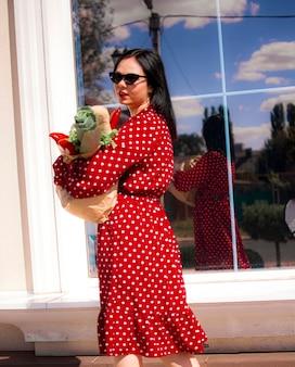 Felice acquirente di generi alimentari. ritratto di bella donna bianca tradizionale in vestito rosso che tiene la borsa della spesa di carta piena di generi alimentari.