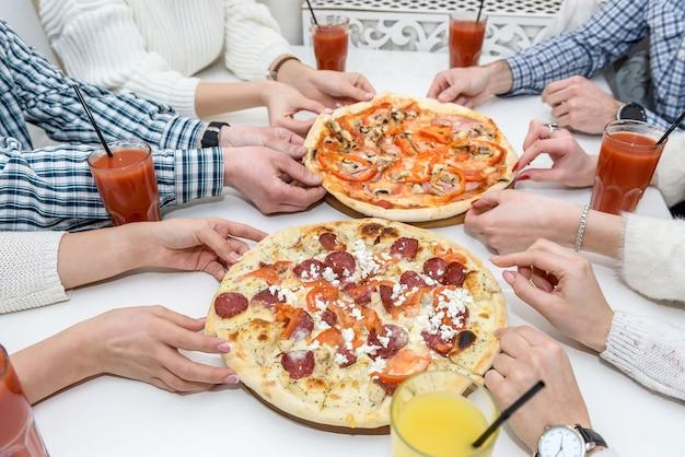 Felice gruppo di amici nella caffetteria che mangia pizza