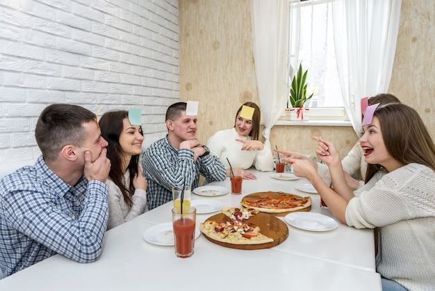 Felice gruppo di amici al bar che mangia pizza