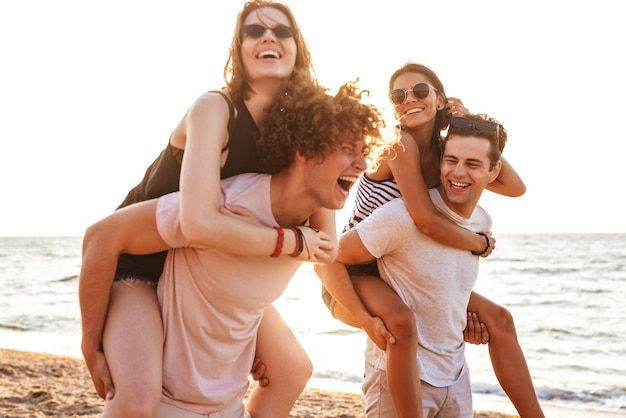 Felice gruppo di amici che amano le coppie che camminano all'aperto sulla spiaggia divertendosi