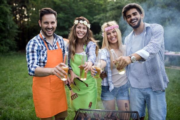 Felice gruppo di amici che fanno un barbecue insieme all'aperto nella natura