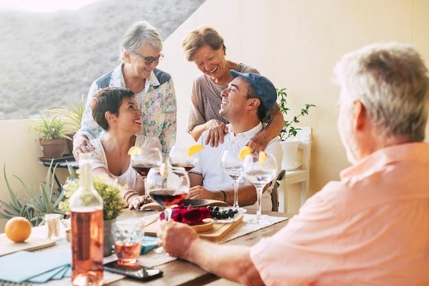 Felice gruppo di amici all'aperto che festeggiano e si divertono insieme durante una cena in terrazza a casa