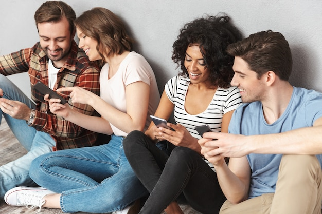 Felice gruppo di amici utilizzando il telefono cellulare in chat.